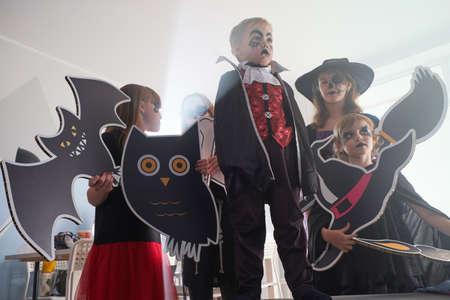 Des enfants sérieux en costumes d'Halloween posent pour le photographe avec des décorations festives dans les mains.