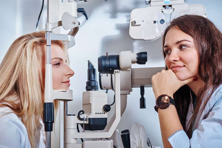 Sceptical optometrist is checking vision of young beautiful woman using special machine. Stockfoto
