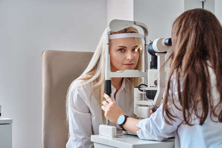 Attractive woman is doing eye test in optical clinic with experienced oculist.