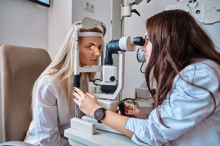 Female patient on eyesight test at optician cabinet with young female oculist.