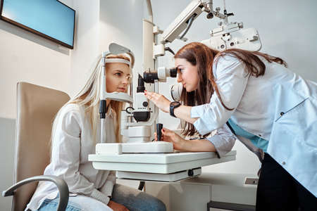 Two attractive females in oculist cabinet, one of them is a doctor, the second one is a patient.