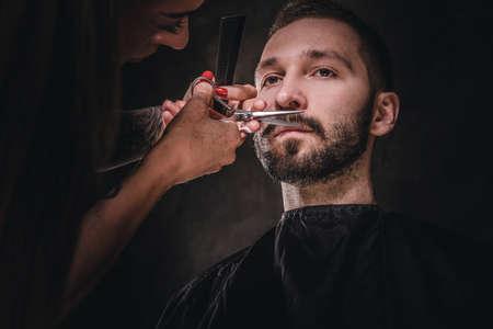 Young gentleman is enjoying mustache and beard trimming at dark barbershop.