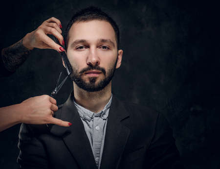 Confident elegant businessman receive a beard care from female with nice manicure.