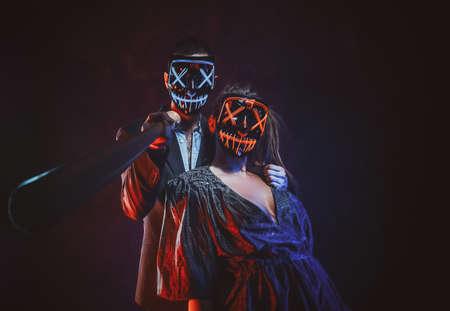 Verrücktes Paar in gruseligen Masken posiert für Fotografen mit Baseballschläger.