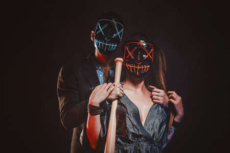 Elegant man with baseball bat in hand is hugging his sexy woman, both of them are wearing masks.