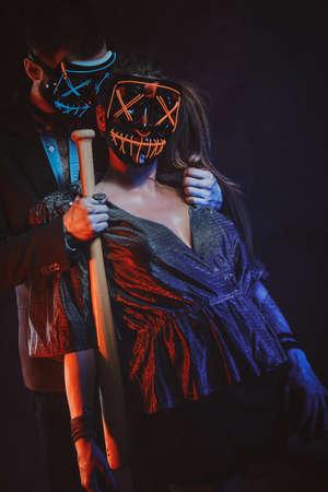 Eleganter Mann mit Baseballschläger in der Hand umarmt seine Frau, beide tragen Masken. Standard-Bild