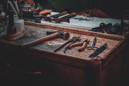 Workplace of cobbler with necessary tools on it at dark workshop. Foto de archivo - 135041192