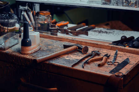 Workplace of cobbler with necessary tools on it at dark workshop. Foto de archivo - 135040013