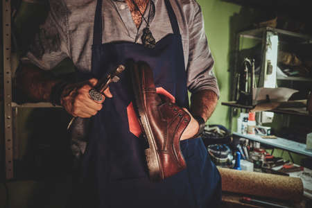 Diligent cobbler is working on shoe sole using special tool at his dark workplace.