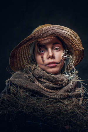 Young artistic woman is posing for photographer in a role of creepy scarecrow. Stockfoto
