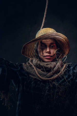 Portrait of young woman on masquerade in dreadful scarecrow costume on the dark background. Stockfoto