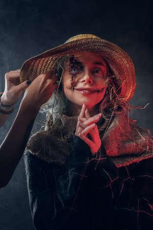 Mujer atractiva tiene un disfraz interesante para Halloween, un espantapájaros espeluznante.