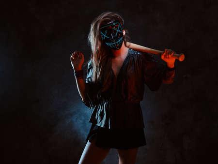 Une femme contrevenante au masque effrayant se tient dans un studio sombre avec une chauve-souris dans les mains.