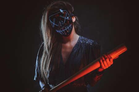 Gesetzesbrecherin in gruseliger Maske steht im dunklen Studio mit Fledermaus in den Händen.