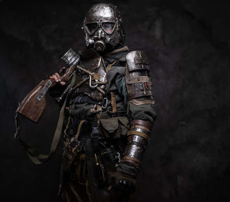 Portrait of a man in  costume of dark apocalypse warrior at photo studio.