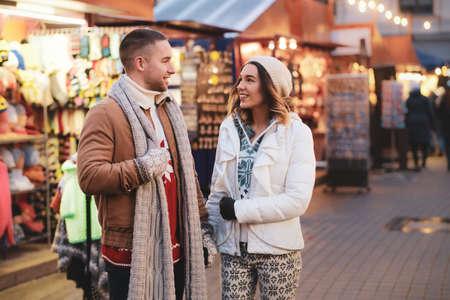 l romantic couple enjoy Christmas day on traditional festive market.