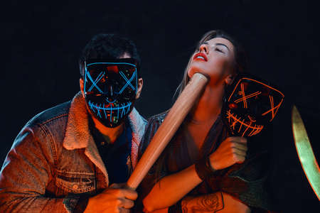 Bandit in scary mask is scaring her attractive girlfriend with baseball bat. 스톡 콘텐츠