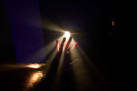 Mans palm is trying to stop rays of the bright light at dark room.