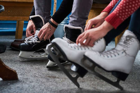 Young couple preparing to a skating. Close-up photo of their hands tying shoelaces of ice hockey skates
