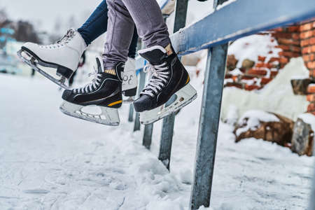 Couple wearing ice skates sitting on a guardrail. Dating in an ice rink. Close-up view of the skates