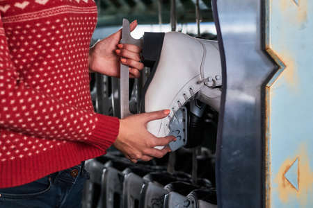 A beautiful girl wearing a warm sweater choosing a pair of skates. Close-up view of the her hands