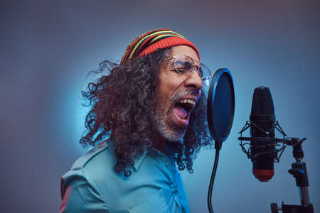 African Rastafarian singer male wearing a blue shirt and beanie emotionally writing song in the recording studio. Isolated on a blue background.