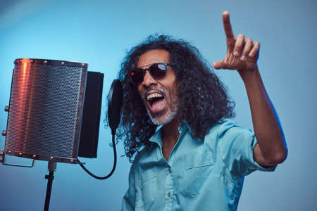 African vocal artist wearing a blue shirt emotionally writing song in the recording studio. Isolated on a blue background.