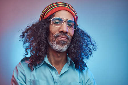 Smiling African Rastafarian male wearing a blue shirt and beanie. Studio portrait on a blue background.