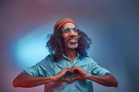 African Rastafarian smokes weed and showing heart symbol and shape with hands. Isolated on a blue background.