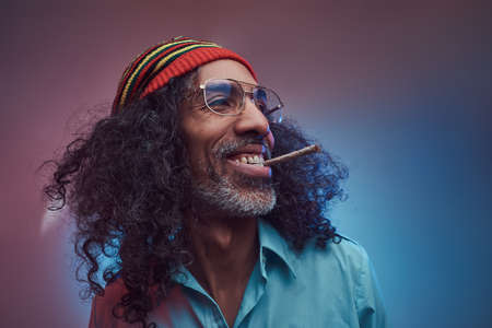 Happy African Rastafarian male smoking cigarettes. Isolated on a blue background.