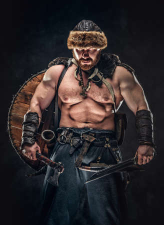 Severe barbarian in warrior clothes, posing on a dark background. 版權商用圖片