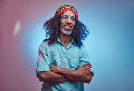 African Rastafarian male smiles and looks at the camera standing with his arms crossed. Studio portrait on a blue background.