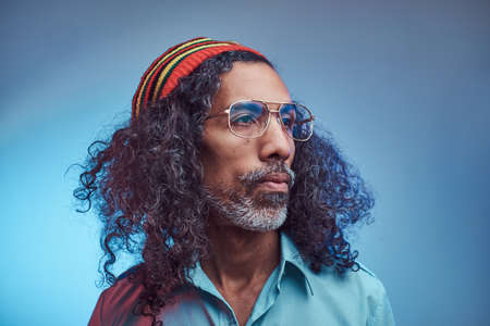 African Rastafarian male wearing a blue shirt and beanie. Studio portrait on a blue background. Stock Photo
