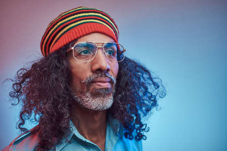 Studio portrait of African Rastafarian male wearing a blue shirt and beanie. Isolated on a blue background.