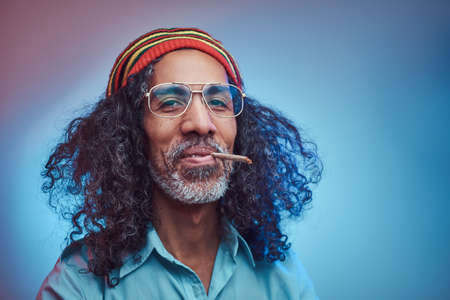Studio portrait of African Rastafarian male smoking cigarettes. Isolated on a blue background.