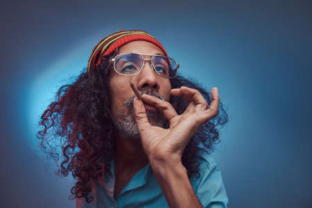 African Rastafarian smokes weed and gets high. Isolated on a blue background.