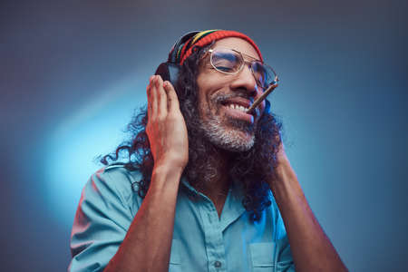Studio portrait of African Rastafarian male enjoys music in headphones and smoking weed. Isolated on a blue background.
