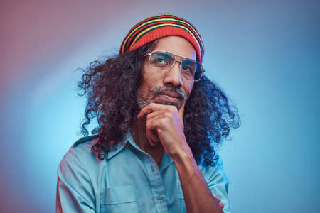 Pensive African Rastafarian male wearing a blue shirt and beanie. Studio portrait on a blue background.