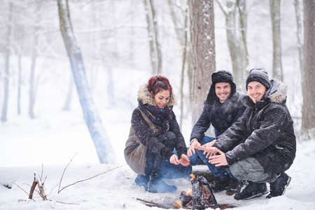 Happy friends warming next to a bonfire in the cold snowy forest