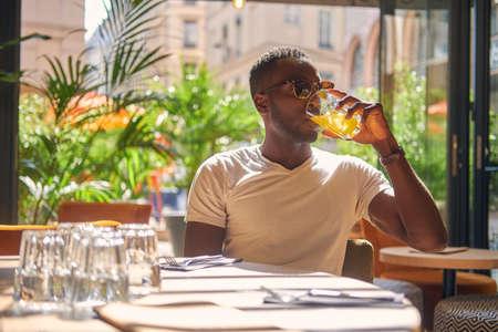 Estudiante estadounidense está bebiendo jugo de frutas en el café en un día caluroso y soleado.