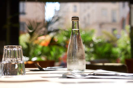 On a sunny day at small restaurant cold bottle of mineral water is standing on the table. Standard-Bild