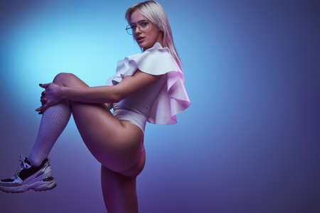 Portrait of a young seductive woman in bodysuit socks and sneakers poses with her leg raised. Isolated on a blue background