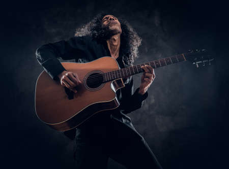 Curly man with guitar is presenting his new acoustic masterpiece at studio.