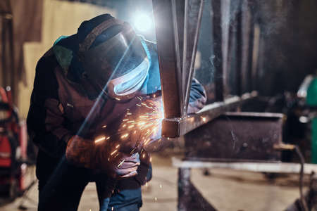 Man is working at metal factory, he is welding a piece of rail using special tools.