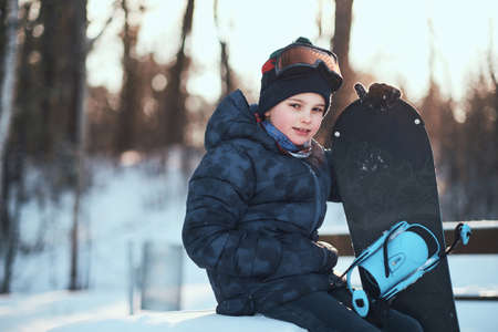 Little kid in protective goggles is posing for photographer with snowboard in winter forest.