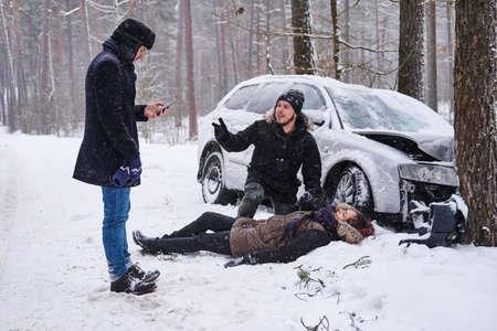 La donna ferita è sdraiata sulla neve dopo un incidente d'auto, l'uomo sta cercando di aiutarla, il secondo uomo sta chiamando un'ambulanza.