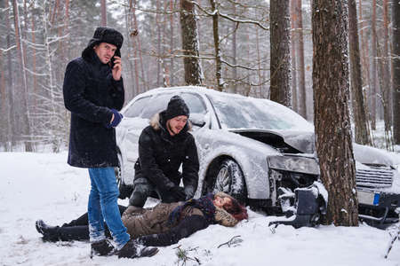 Injured woman is lying on the snow after car crush, man is trying to help her, the second man is calling ambulance.