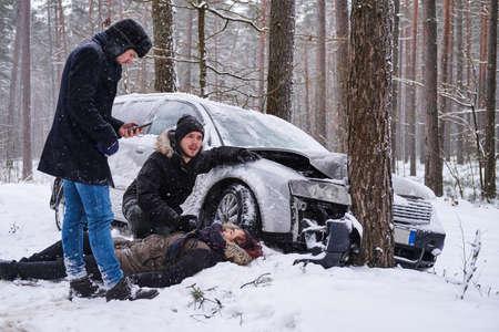 La donna ferita è sdraiata sulla neve dopo un incidente d'auto, l'uomo sta cercando di aiutarla, il secondo uomo sta chiamando un'ambulanza. Archivio Fotografico