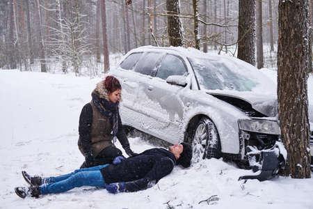 L'uomo ferito è sdraiato sulla neve dopo un incidente d'auto e la donna sta cercando di aiutarlo.