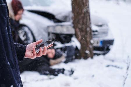 L'uomo tiene in mano il cellulare per chiamare un'ambulanza mentre la donna sta controllando il maschio ferito dopo un incidente d'auto.